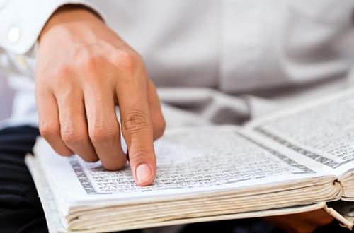 person reading quran seeking knowledge